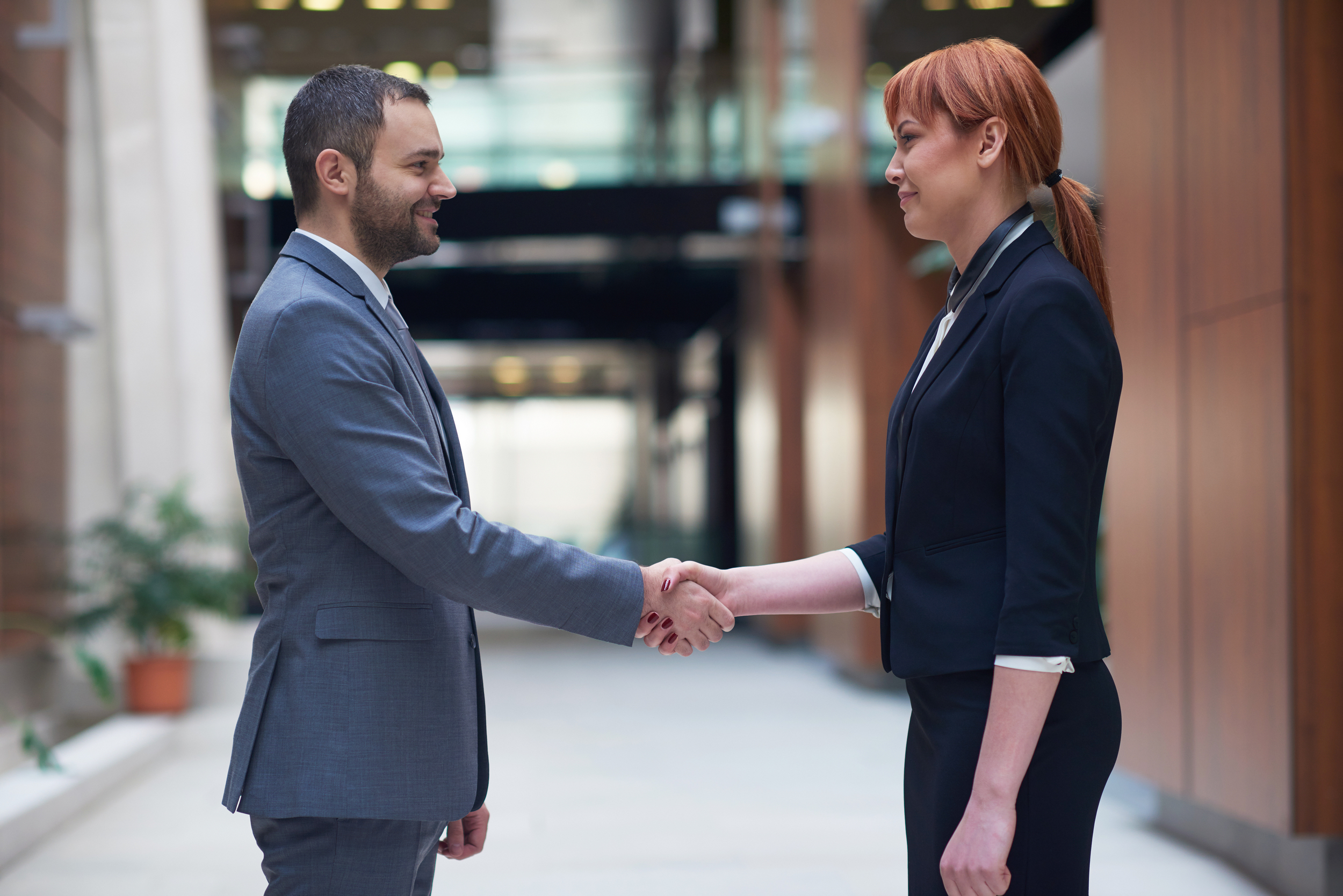 partnership concept with business man and woman hand shake and take agreement in modern office interior